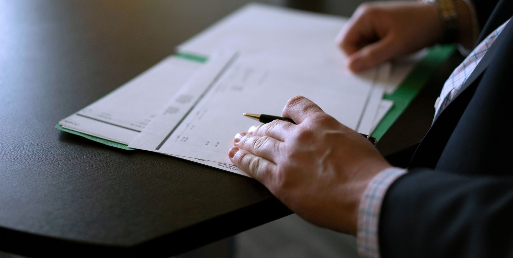 Shot of documents on a table with hand holding a pen.